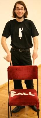 Stuhl mit Aufschrift BALL aus Kreppband, Regisseur im Hintergrund