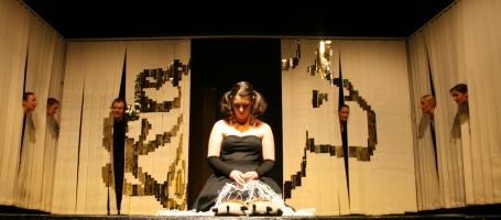 Antigone (Alessa, in der Mitte kniend) betet mit dem Fischernetz ihrer Mutter einen Rosenkranz für ihren toten Vater Ödipus. Der Chor kommentiert und steckt dabei die Köpfe durch Lamellenvorhänge an den Bühnenrändern.