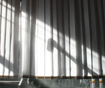 Eine Sprühdose mit B1-Imprägnierung als Schattenspiel hinter dem Lamellenvorhang. Sprühdose gehalten von Annika Packmor. Foto vom 13.04.2009.