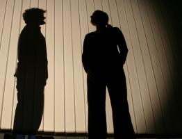 Ödipus (Martin, links) steht hinter der Schattenwand und wird von Kreon (Maren, rechts) nach seinen Wünschen befragt.