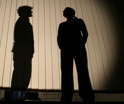 Ödipus (Martin Lhotzky, links) steht am Ende des 1. Teils von Ödipedia hinter einer Schattenwand und wird von Kreon (Maren Peter, rechts) befragt und verspottet. Foto vom 19.04.2009.