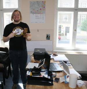 Vinzenz Rothenburg steht in unserem AntikEkstase-Büro in der Brotfabrik und hält eine Holzeule namens Edwin in der Hand