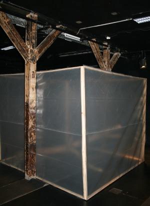 Bühnenraum der Brotfabrik mit Kubus aus Folie, dahinter Baumstamm