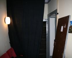 In einem Gang der Brotfabrik: Ausgehängte Türe, schwarzer Vorhang